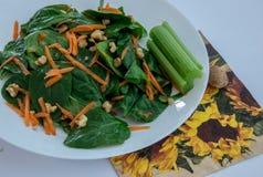 Close up da salada verde com espinafres, cenoura e porcas com aipo fotografia de stock royalty free