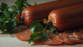 Close-up da salsicha do salame no fundo de madeira Quadro Salame na placa de corte de madeira filme