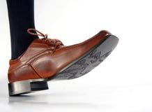 Close-up da sapata masculina que pisa no fundo branco Fotografia de Stock