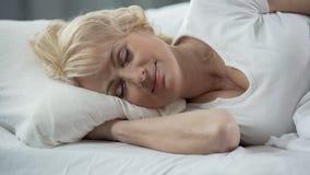 Close-up da senhora madura loura bonita que encontra-se na cama, sono saudável, aposentadoria filme