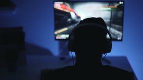 Close-up da silhueta do indivíduo que joga o jogo de vídeo eletrônico em casa tarde na noite