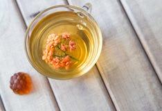 Close up da vista superior do copo do chá com a flor brilhante na tabela de madeira com doce de fruta Ainda vida com copo de chá Imagem de Stock Royalty Free