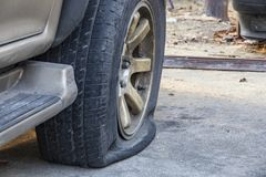 Close-up of damaged flat tire of car on parking stock photo