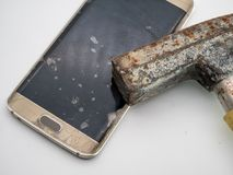 Close-up of damaged smartphone display with hammer stock photography