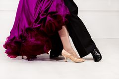 Close up of dancers feet. Ballroom dancers on the dance floor. A man in trousers, a woman in a magnificent ball gown royalty free stock image