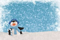 Close up on a dancing penguin, blue bokeh lights in background and snowflakes in border. Christmas greeting card concept stock photos