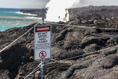Close up of Danger no tresspassing sign that marks safe viewing spot for bright red lava flow of volcano in Hawai Royalty Free Stock Images