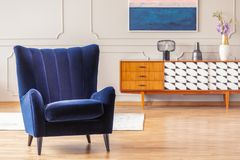 Dark blue armchair with a vintage cabinet in the background in a living room interior stock photos