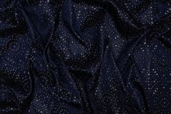 Close up of dark blue fabric with ornaments and glitter.  stock photography