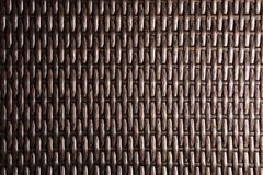 Close-up Dark brown background is an element of wicker furniture made of polymer fibers. Synthetic luxury substrate.  stock images