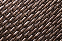 Close-up Dark brown background is an element of wicker furniture made of polymer fibers. Synthetic luxury substrate.  stock photography