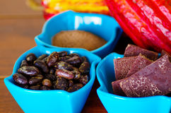 Close up of a dark dry cocoa bean, pieces of chocolate and powdered cocoa inside of a blue plastic bowl Royalty Free Stock Photo