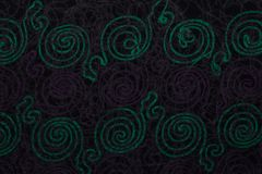 Close up of dark fabric with green and violet patterns with textile texture background.  stock image