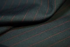 Close up dark gray fabric of suit with red line strip. Photoshoot by depth of field for object stock photo