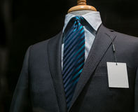 Dark Gray Striped Jacket With A Blank Tag (Horizontal). Close-up of a dark gray striped jacket with striped blue tie and a blank white tag on the left lapel stock photos