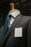 Dark Gray Striped Jacket With A Blank Tag (Vertical). Close-up of a dark gray striped jacket with striped blue tie and a blank white tag on the left lapel Stock Image