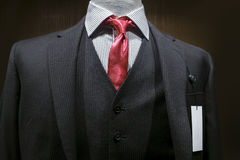Dark Gray Striped Suit With A Blank Tag. Close-up of a dark gray striped suit with striped white shirt, red tie and a blank white tag on the left lapel. Clipping Stock Photo