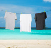Close up of a dark grey, white and grey t-shirts on the rope. Stock Photo