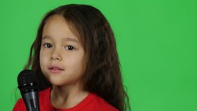 Close-up dark-haired baby with microphone on green background. Slow motion. Close-up dark-haired baby singing with microphone doing a little dance getting ready stock video footage