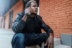Dark-skinned annoyed man talking by mobile phone and sitting on concrete steps. royalty free stock photos