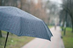 Close-up of dark umbrella during rain. Stock Images