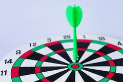 Close up dartboard. With arrow in center focused point isolated on white background represents business goal concept Stock Photo