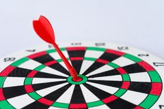 Close up dartboard. With arrow in center focused point isolated on white background represents business goal concept Royalty Free Stock Image
