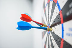 Close up of dartboard with dart arrows in center Stock Image