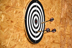 Close up of darts arrows being stuck in the target board Stock Photos