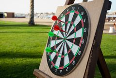 Close up of darts with red and green arrows on green grass background. Darts game on vacation. Funny game for tourist on the beach royalty free stock photo