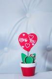 Close up das alianças de casamento na pétala da flor artificial na forma de um coração Imagem de Stock Royalty Free