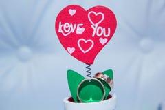 Close up das alianças de casamento na pétala da flor artificial na forma de um coração Imagens de Stock Royalty Free