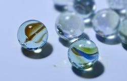 Close-up das bolas transparentes de vidro com as decorações multi-coloridas incomuns para dentro com um fundo borrado macio foto de stock