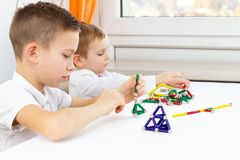 Close-up das crianças que jogam o jogo de mesa ao sentar-se na tabela em casa, lotes de ímãs coloridos para o desenvolvimento inf fotos de stock royalty free