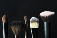 Close up das escovas do cosmético isoladas no fundo preto fotos de stock