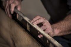 Close up das mãos ásperas ásperas do ` s do carpinteiro usando a ferramenta nivelada velha na borda da placa de madeira imagem de stock