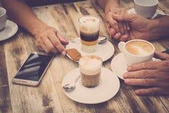 Close-up das m?os com copos e telefone celular de caf? em um caf? com tabelas de madeira - caf? da manh? da manh? do alimento e d fotografia de stock royalty free