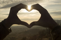 Close up das mãos coração-dadas forma no céu do por do sol imagem de stock royalty free