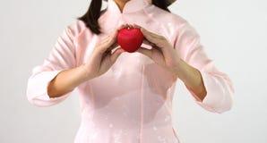 Close up das mãos da jovem mulher com forma do coração da bola Imagem de Stock Royalty Free