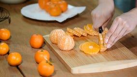 Close up das mãos da mulher que cortam a tangerina do cal video estoque