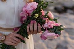 Close up das mãos da mulher que guardam o eustoma cor-de-rosa foto de stock