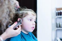 Close-up das mãos da mulher que preparam o cabelo do menino fotos de stock royalty free