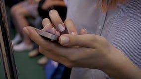 Close-up das mãos da mulher usando Smartphone que está no carro de metro filme