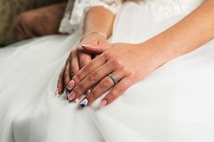 Close up das mãos da pessoa fêmea nova, mulher, noiva no vestido de casamento, sentando-se pela janela, cortinas brancas com diam imagem de stock