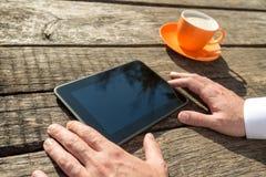 Close up das mãos de um homem que guarda a tabuleta digital vazia e o c imagem de stock royalty free