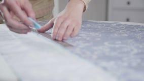 Close-up das mãos de uma costureira Na tela linha de corte revestida video estoque