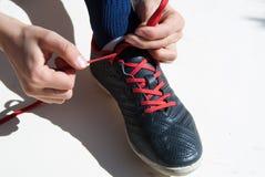 Close up das mãos de uma criança que amarra uma sapata do futebol no fundo branco imagens de stock