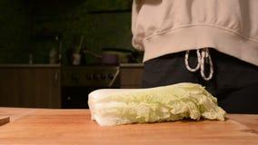 Close-up das mãos de uma menina na cozinha da casa em uma couve de madeira de Pikinsky das facas da placa de corte para a salada  video estoque