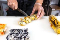 Close up das mãos do cozinheiro chefe que rolam acima dos cortes do sushi em parcelas na cozinha imagem de stock