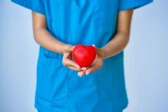 Close up das mãos do doutor da jovem mulher com forma do coração da bola Imagens de Stock Royalty Free